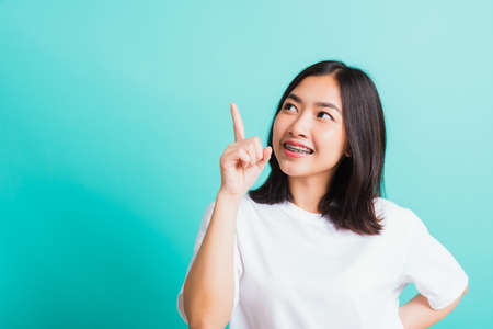 Portrait of Asian teen beautiful young woman smile have dental braces on teeth laughing point finger side away blank copy space, studio shot isolated on blue background, medicine and dentistry concept Standard-Bild