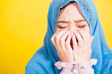 Asian Muslim Arab, Portrait of happy beautiful young woman religious wear veil hijab she sad crying using hand wiping tears in her eyes, studio shot isolated on yellow background with copy space