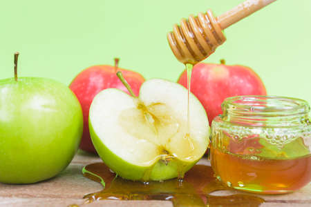 Jewish holiday, Apple Rosh Hashanah, the photo have honey in jar and drop honey on green apples on wooden with green background