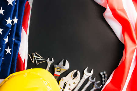 Labor day concept, Top view flat lay of different kinds wrenches with American flag on black. First Monday in September, creation of labor movement and dedicated to social of the American worker