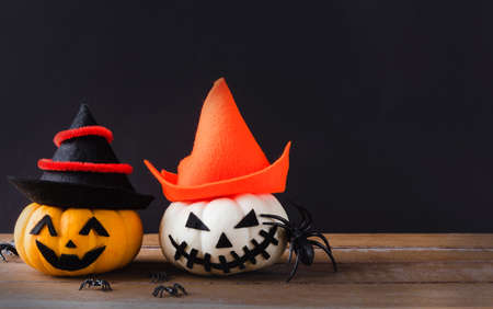 Funny Halloween day party concept ghost pumpkins head jack lantern scary smile wear hat and spider on wooden table and black background, studio shot isolated, Holiday decoration Stock Photo