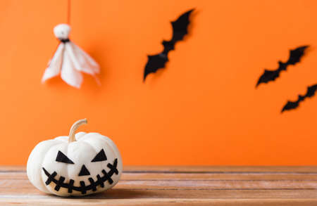 Funny Halloween day decoration party, Cute pumpkin ghost spooky jack o lantern face, black spider and bats on wooden table, studio shot isolated on an orange background, Happy holiday concept Stockfoto