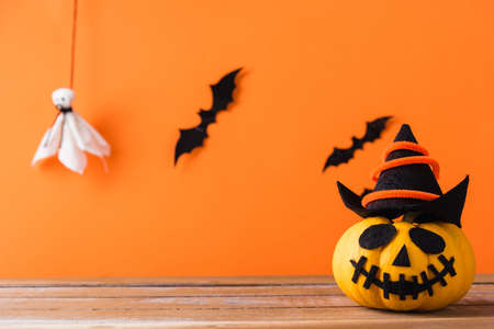 Funny Halloween day decoration party, Cute pumpkin ghost spooky jack o lantern face wear hat, black spider and bats on wooden table, studio shot isolated on an orange background, Happy holiday concept