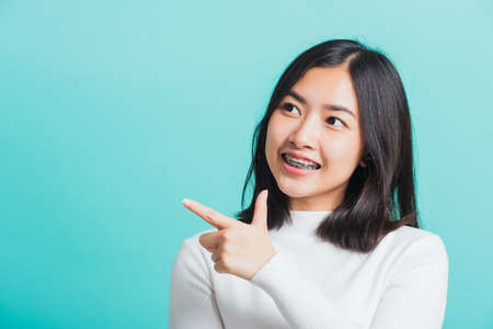 Portrait of Asian teen beautiful young woman smile have dental braces on teeth laughing point finger side away blank copy space, studio shot isolated on blue background, medicine and dentistry concept