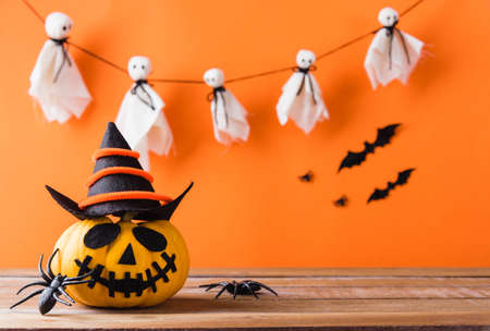 Funny Halloween day decoration party, Cute pumpkin ghost spooky jack o lantern face wear hat, black spider and bats on wooden table, studio shot isolated on an orange background, Happy holiday concept Stockfoto