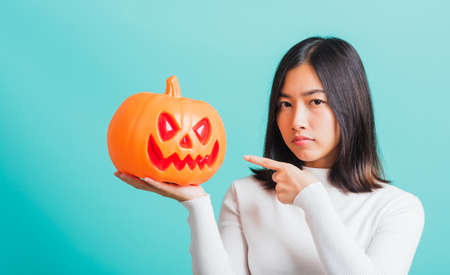 Portrait of Asian beautiful young woman holding orange model pumpkins, funny happy female with ghost pumpkins, studio shot isolated on blue background