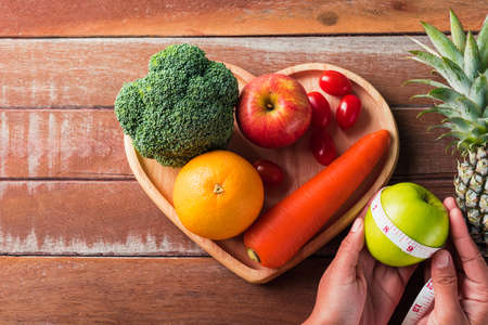 World food day, Top view of various fresh organic fruit and vegetable in heart plate and woman use hands hold the plate, studio shot on wooden table, Healthy vegetarian food concept