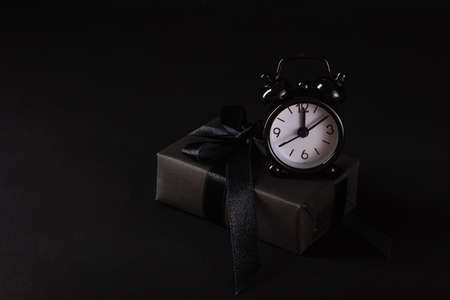 Black Friday sale shopping concept, Top view of gift box wrapped in black paper and black bow ribbon and black alarm clock, studio shot on black background Imagens