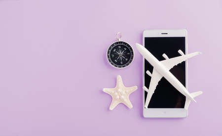World Tourism Day, Top view of minimal model plane, airplane, starfish, alarm clock, compass on smartphone blank screen, studio shot isolated on a purple background, accessory flight holiday concept Imagens