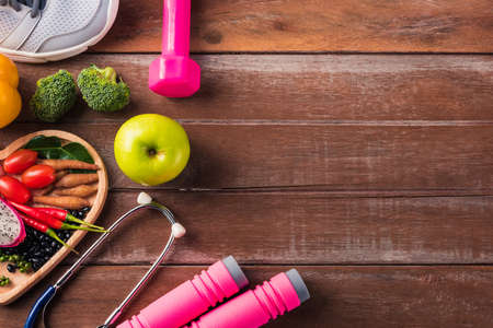 Top view of fresh organic fruit and vegetable in heart plate, shoes, sports equipment and doctor stethoscope, studio shot on wooden gym table, Healthy diet vegetarian food concept, World food day 版權商用圖片