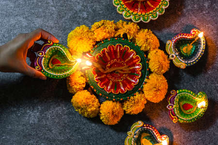 Close up woman hand being lit clay light fire on Diya or oil lamp studio shot on black wooden background, Decoration of Hinduism rangoli, Happy celebration Deepavali or Diwali festival concept