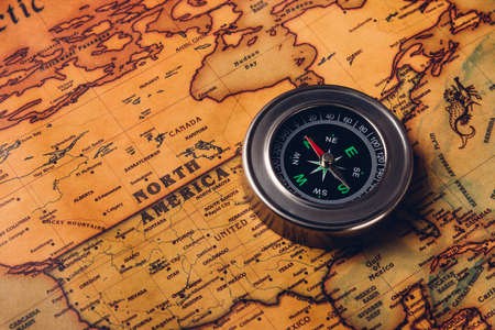 Old compass discovery on vintage paper antique world map background, Retro style cartography travel geography navigation, Pirate navigate the geography