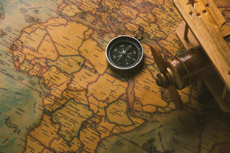 Old compass discovery and wooden plane on vintage paper antique world map background, Retro style cartography travel geography navigation