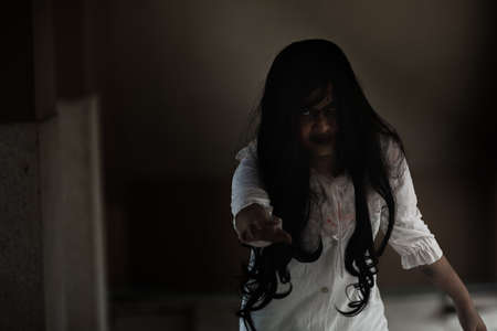Girl zombie in blood. Asian Woman ghost with blood. Horror scary fear in house dark tone raise hand and reach out. Closeup hair covering the face her eye looking to camera, Halloween festival concept