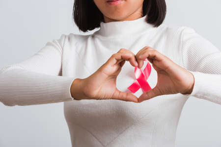 Breast cancer awareness healthcare and medicine concept. Close up Asian woman wear shirt she have pink breast cancer awareness ribbon on chest show symbol heart framing from fingers, white background Stockfoto