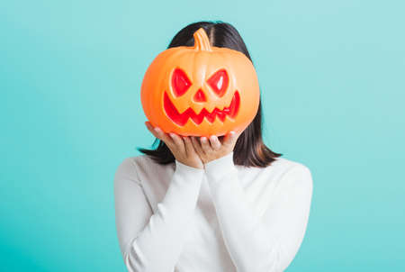 Portrait of Asian beautiful young woman holding orange model pumpkins at her head, funny happy female with ghost pumpkins, studio shot isolated on blue background Stockfoto