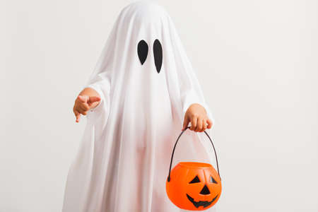 Funny Halloween Kid Concept, little cute child with white dressed costume halloween ghost scary he holding orange pumpkin ghost on hand, studio shot isolated on white background Stockfoto