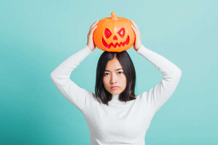 Portrait of Asian beautiful young woman holding orange model pumpkins and put it on the head, funny happy female with ghost pumpkins, studio shot isolated on blue background Stockfoto