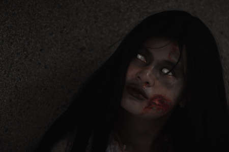 Girl zombie in blood. Asian Woman ghost with blood. Horror creepy scary fear she sitting in a dark house. Hair covering the face, Halloween festival concept