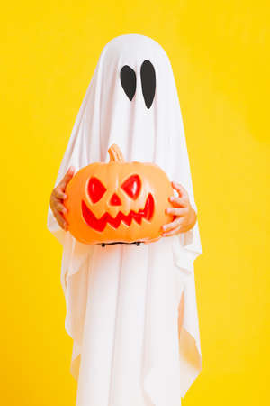 Funny Halloween Kid Concept, little cute child with white dressed costume halloween ghost scary he holding orange pumpkin ghost on hand, studio shot yellow on white background Stockfoto