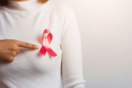 Breast cancer awareness healthcare and medicine concept. Close up Asian woman wear white shirt pointing finger to pink breast cancer awareness ribbon, studio shot isolated on white background