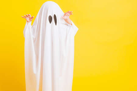 Funny Halloween Kid Concept, Closeup a little cute child with white dressed costume halloween ghost scary, studio shot isolated on yellow background Stockfoto