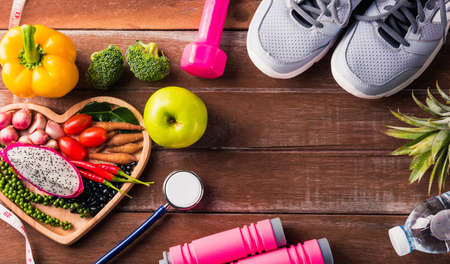 Top view of fresh organic fruit and vegetable in heart plate, shoes, sports equipment and doctor stethoscope, studio shot on wooden gym table, Healthy diet vegetarian food concept, World food day Stockfoto