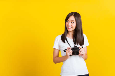 Portrait of happy Asian beautiful young woman photographer holding vintage digital mirrorless photo camera on hands, studio shot isolated on yellow background, lifestyle teenager hobby travel concept Stockfoto
