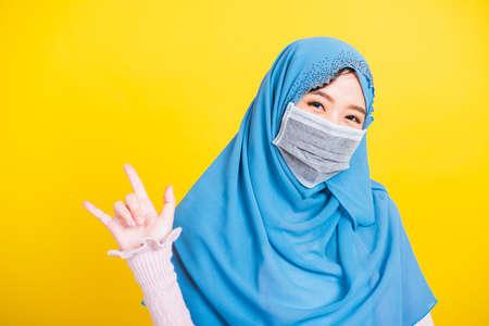 Asian Muslim Arab, Portrait of happy beautiful young woman Islam religious wear veil hijab and face mask protect quarantines disease coronavirus show hand finger