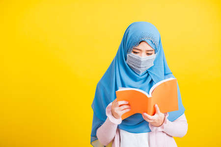 Asian Muslim Arab, Portrait of happy beautiful young woman religious wear veil hijab and face mask protective to prevent coronavirus she hold book on hand and open reding it on yellow, Back to college Stockfoto