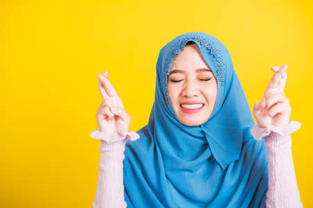 Asian Muslim Arab, Portrait of happy Asian beautiful young woman Islamic religious wear veil hijab she smiling and holding fingers crossed for good luck, studio shot isolated on yellow background