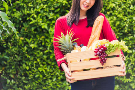 Portrait of Asian beautiful young woman farmer standing she smile and holding full fresh food raw vegetables fruit in a wood box in her hands on green leaves background