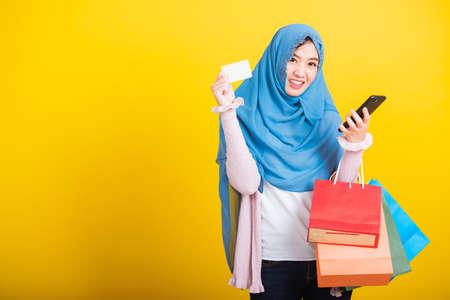 Asian Muslim Arab, Portrait of happy beautiful young woman Islam religious wear veil hijab funny smile she using smartphone on hand and hold shopping bags, studio shot isolated on yellow background