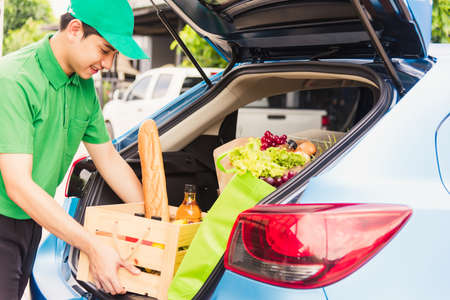 Asian delivery man grocery prepare service giving fresh vegetables food and fruit full in wooden basket on back car to send woman customer at door home after pandemic coronavirus, Back to new normal