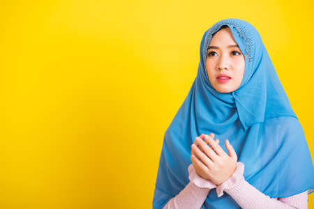 Asian Muslim Arab, Portrait of happy beautiful young woman religious wearing veil hijab she henna decorated hands praying to Allah God, isolated on yellow background, Eid Mubarak and soul fasting