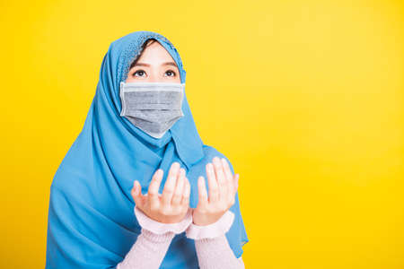 Asian Muslim Arab, Portrait beautiful young woman religious wear veil hijab and face mask protect to prevent coronavirus she henna decorated hands praying to Allah God, isolated on yellow background