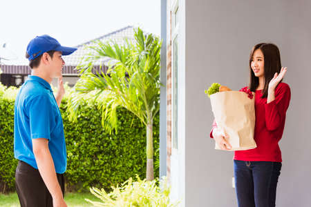 Asian young delivery man in blue uniform making grocery service giving fresh vegetables and fruits and food in paper bag to woman customer at front house after pandemic coronavirus, Back to new normal Stockfoto