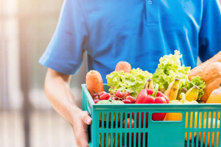 Asian grocery store delivery man wearing blue uniform and face mask protect he delivering fresh food vegetable in plastic box at door front home after coronavirus outbreak, back to new normal concept Stockfoto