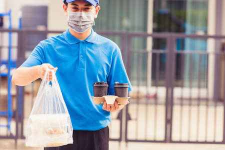 Asian young delivery man in blue uniform wearing face mask making grocery service giving rice food boxes plastic bags and coffee at front house under pandemic coronavirus, Back to new normal concept Stockfoto