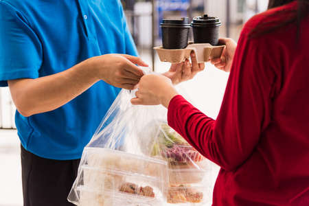Asian young delivery man in blue uniform he making grocery service giving rice food boxes plastic bags to woman customer receiving front house under pandemic coronavirus, Back to new normal concept Stockfoto