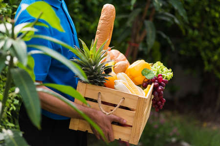 Asian man farmer wears delivery uniform he holding full fresh vegetables and fruits in crate wood box in hands ready give to customer harvest organic food on the garden place green leaves background