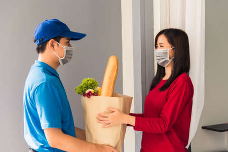 Asian young delivery man in uniform wear protective face mask he making grocery service giving fresh food to woman customer receiving front house under pandemic coronavirus, Back to new normal concept