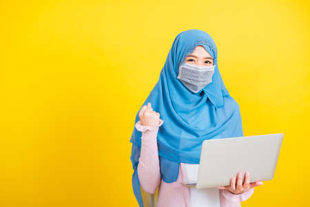 Asian Muslim Arab Portrait of happy beautiful young woman Islam religious wear veil hijab and face mask protect she quarantines disease coronavirus hold laptop computer and raise hand to indicate glad