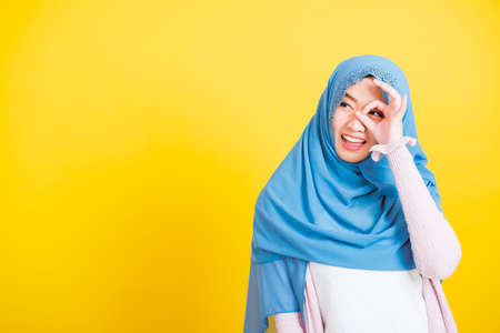 Asian Muslim Arab, Portrait of happy beautiful young woman Islam religious wear veil hijab funny smile she show gesture fingers in okay gesture symbol, OK sign over her eyes isolated yellow background Stockfoto