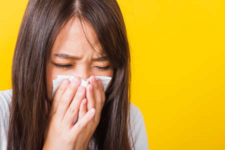Portrait of Asian beautiful young woman sad she crying wipe the mucus with tissue, Close up of pretty girl sneezing sinus using towel to wipe snot from nose, studio shot isolated on yellow background