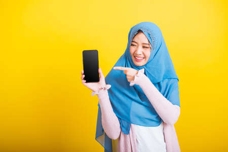 Asian Muslim Arab, Portrait of happy beautiful young woman Islam religious wear veil hijab funny smile she showing blank screen smart mobile phone and point screen isolated on yellow background