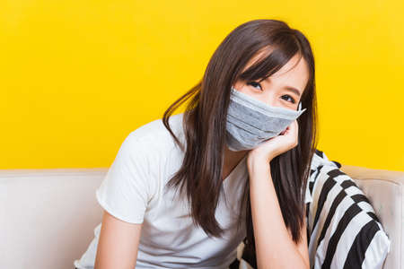 Portrait Asian of beautiful young woman sitting on sofa wearing medical face mask protective during Coronavirus studio shot isolated on yellow background