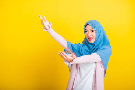 Asian Muslim Arab, Portrait of happy beautiful young woman Islam religious wear veil hijab funny smile she open arms for hug or raise hand to pick up items receive something from above isolated yellow
