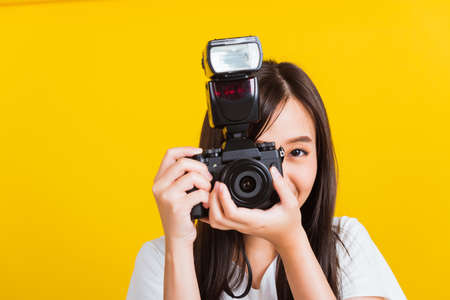 Portrait of happy Asian beautiful young woman photographer smile take picture and looking viewfinder on retro digital mirrorless photo camera ready to shoot, studio shot isolated on yellow background
