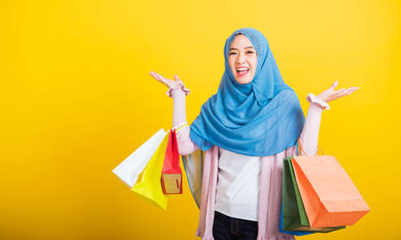 Asian Muslim Arab, Portrait of happy beautiful young woman Islam religious wear veil hijab funny smile she holding colorful shopping bags so glad shopping bags hand raise in studio isolated on yellow Stockfoto